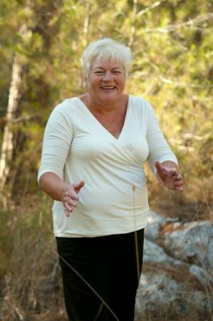 Smiling Senior woman exercising in leafy park