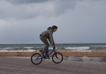 Teenager rides a bicycle along the seafront   Stock Photo