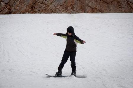 Teen boy snowboarding on the snow mountains   photo