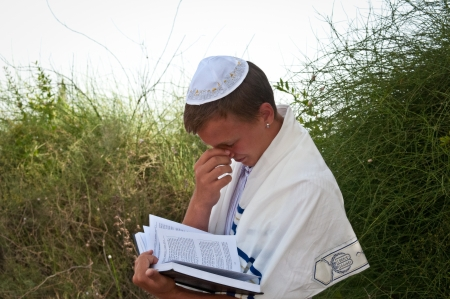 siddur: Religious Jewish teenager with a book in hand .