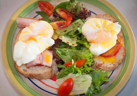 benedict: Eggs Benedict on toasted muffins with ham and leaf salad and tomato .