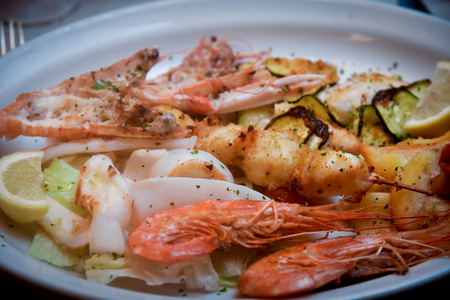 Grilled grilled seafood with limon on white plate . Stock Photo