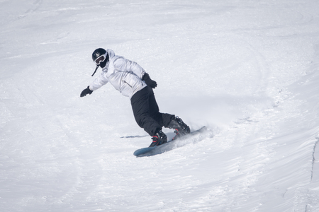 Young man a snowboarder  descends a backcountry at  from a slope . Stock Photo