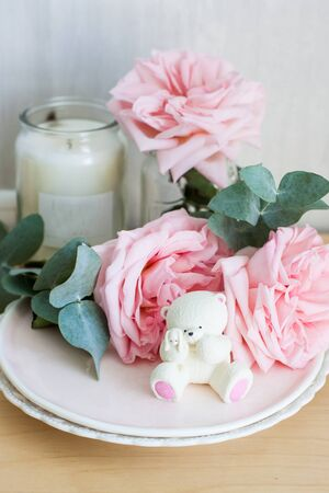 White chocolate teddy bear with little bunny in his hands. Roses and candles on the background.