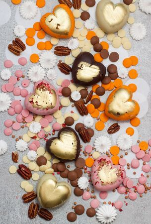 Assorted pink, orange, brown and green chocolate hearts with meringues, pecan nuts and chocolate drops