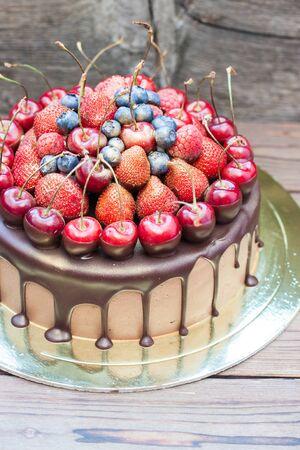 Chocolate cake with fresh cherries, strawberries, raspberries and blueberries on wooden background