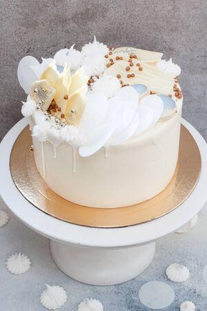 Elegant white wedding cake with chocolate decoration, meringues and macaroons on grey background.
