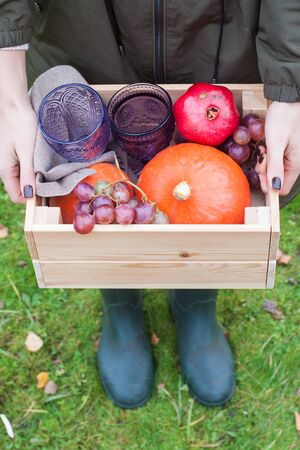 Hands holding wooden box with vegetables: pumpkin, grape, pomegranate and glasses of wine. Close up.