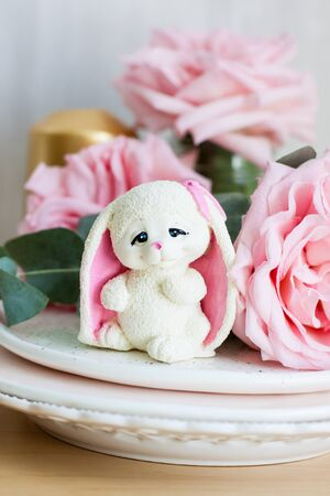White chocolate tender easter bunny with pink ears. Fresh roses and golden candle on the background
