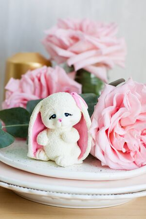 White chocolate bunny with pink ears with roses and golden candle on the background