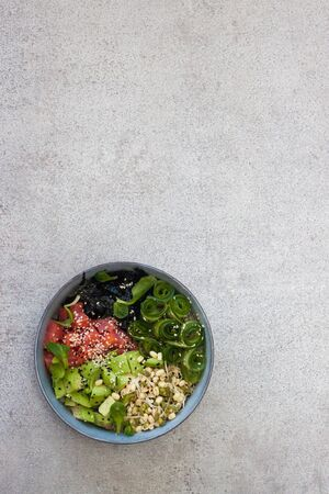 Poke bowl with rice, avocado, pickled cucumber and crispy sea kale. Plain grey background. Isolated. Stockfoto