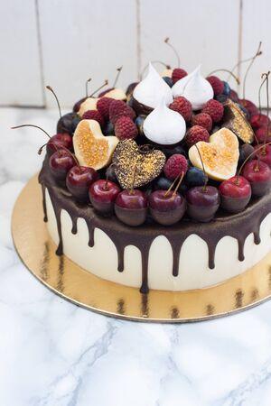 Vanilla cheesecake decorated with melted dark chocolate, fresh berries, cherries, chocolate hearts and meringues. White rustic background. Imagens