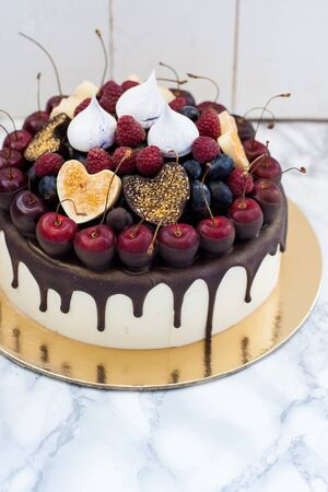 Vanilla cheesecake decorated with melted dark chocolate, fresh berries, cherries, chocolate hearts and meringues. White rustic background.