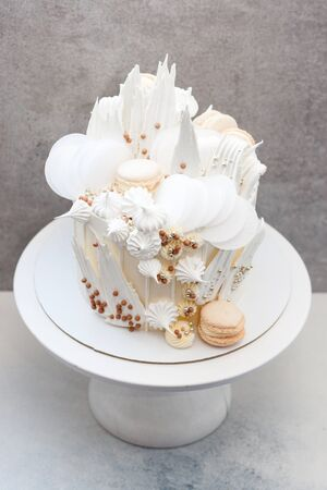 Modern grey colored cake with white chocolate decoration, macaroons, meringues, waffle paper. Grey background.