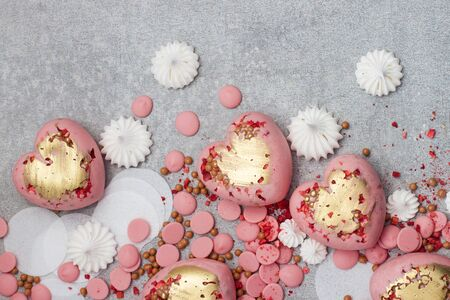 Pink hearts from tempered chocolate with chocolate drops, meringues and dried berries