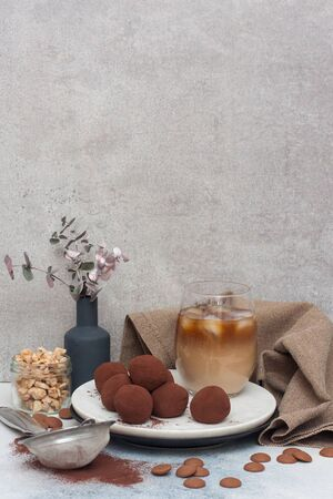 Cold coffee liqueur with chocolate truffles, rolled in cocoa powder on grey background