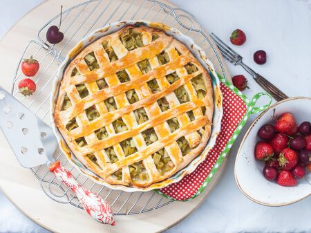 Homemade rhubarb pie on cooling rack. Decorated with fresh summer berries. Top view. White background.