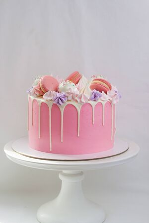 Tender pink cake decorated with melted white chocolate, macaroons, meringues, cake pops and candies on white cakestand. Plain background.