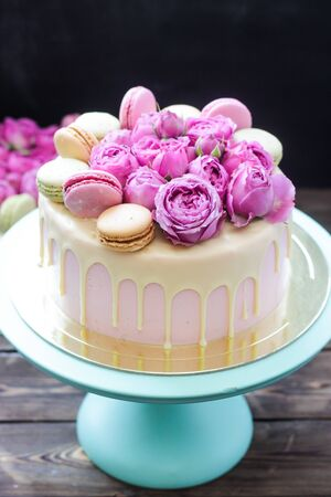 Modern pink cake with melted chocolate, fresh roses and macaroons. Concept for Wedding , St. Valentine's Day, Mother's Day, Birthday Cake. Banque d'images