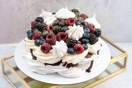 Meringue cake Pavlova with fresh ripe raspberry, blackberry and blueberry, and whipped cream on grey background.