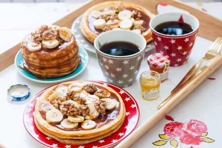 Breakfast tray with pancakes with bananas, maple syrup and nuts, cup of coffee and honey. Morning food concept.