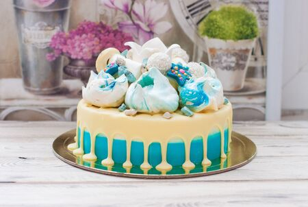 Blue cake with melted white chocolate, meringues and fondant crown. Rustic background.