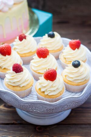 Vanilla cupcakes with cream cheese frosting and fresh berries, blueberry and strawberry. Rustic background.