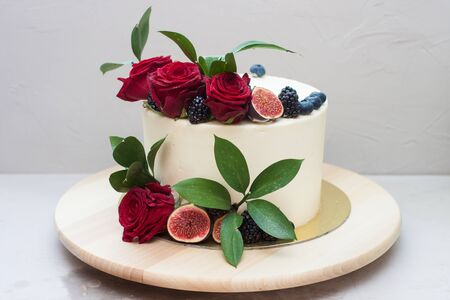 Elegant wedding cake decorated with fresh red roses, green leaves, figs and blueberry. Plain background.