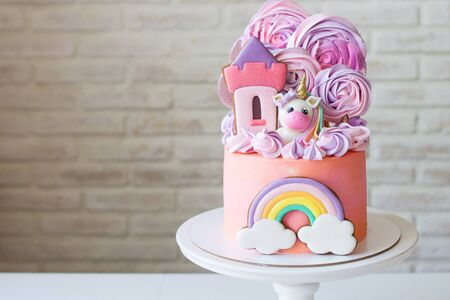 Cute pink birthday cake for a little girl with fondant unicorn, gingerbread princess castle, rainbow and meringue clouds.