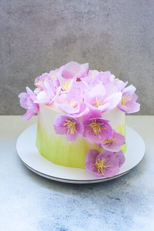 Tender green birthday cake with purple paper flowers on grey background.