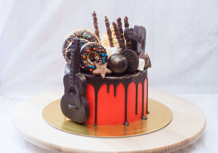 Red cake with melted chocolate, marshmallow, candies, toffees, guitars, donuts, cake pops and stars decoration. Stock Photo