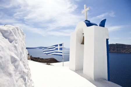 Church in Oia village on Santorini and a Greek Flag photo