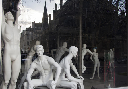 layman: Paris, France - April 15, 2013: Showcase a sports shop. Mannequins. In the glass reflected the evening street. Editorial