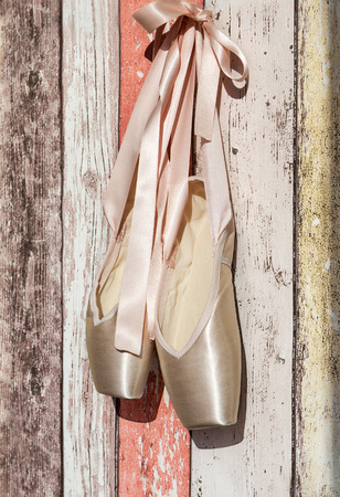 pointe shoes: Pink pointe shoes, ballet shoes on old wooden background. Vertical composition.