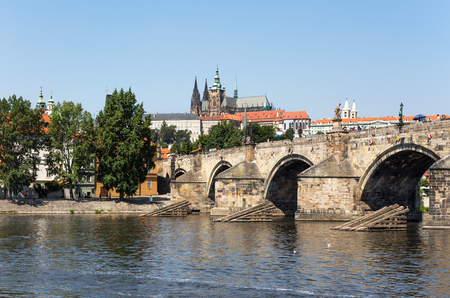 Tourists walk along the Charles Bridge on a summer sunny day. Prague, Czech Republic.