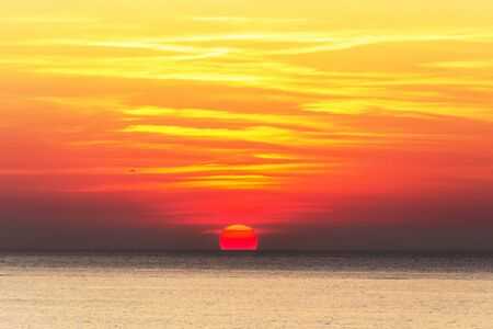 A breathtaking view of the picturesque yellow-red sunrise over the sea. Bright yellow-red sky, red sun rises over the Black Sea. Sts. Constantine and Elena Resort, Varna, Bulgaria. Stock fotó