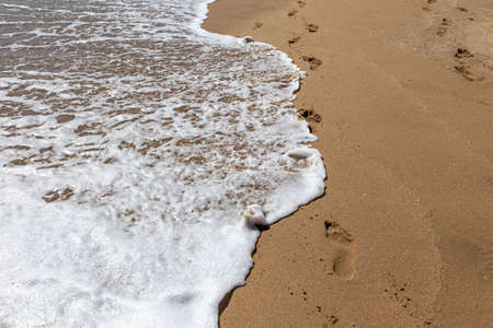 The foamy sea wave running onto the sandy shore washes away the footprints. Reklamní fotografie