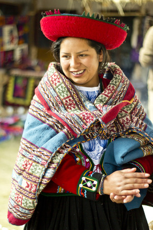 CHINCHERO, PERU - JUNE 6, 2013: Woman dressed traditionally while working on a homemade wool clothes industry. June 6, 2013 in Chinchero, Peru