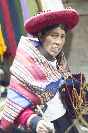CHINCHERO, PERU - JUNE 4, 2013: Woman dressed traditionally while working on a homemade wool clothes industry. June 4, 2013 in Chinchero, Peru