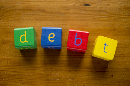 sums: Colorful wooden blocks spelling the word DEBT
