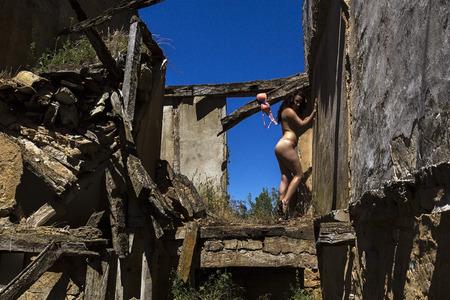 the naked girl: chica desnuda posando en casa en ruinas Foto de archivo
