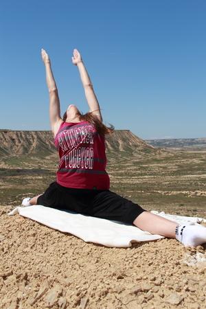sportwoman: young girl doing yoga in desert Stock Photo