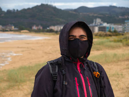 young woman with mas in the beach in pandemic winter