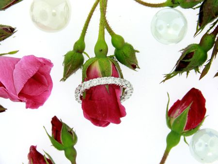 Diamond engagement ring with red roses isolated on white