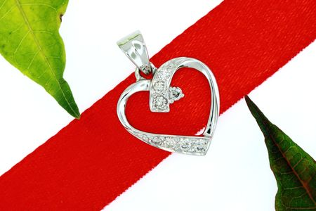 closeup of diamond heart pendant on red ribbon with green leaves isolated on white
