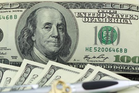 one hundred dollar bill closeup with a gold key and pen - finance concept