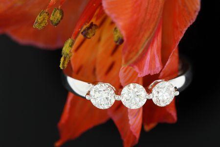 three stone diamond engagement ring on black background