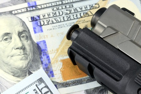 financial security: Hand Gun with American Currency - Hundred Dollar Bill Financial Security concept