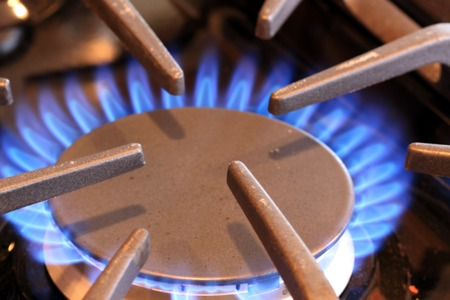 butane: Natural gas stove burner with blue flame Stock Photo