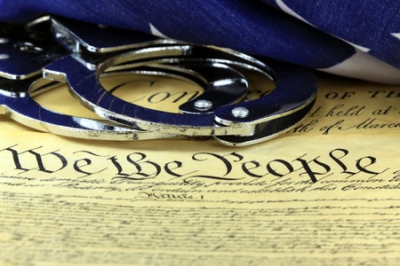 Handcuffs on US Constitution - Fourth Amendment rights Stock Photo
